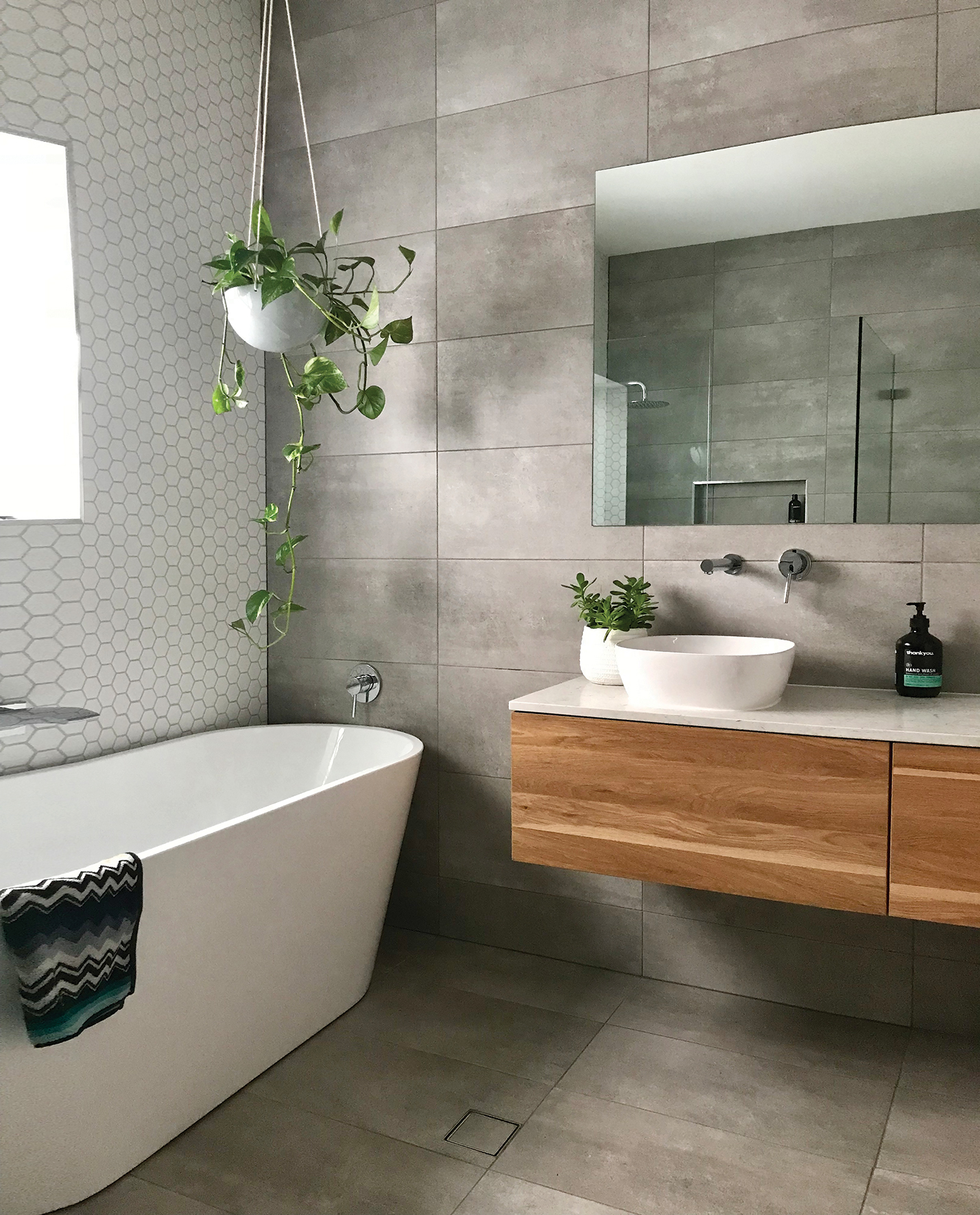 bathroom with vanity mirror and bathtub with gray tile
