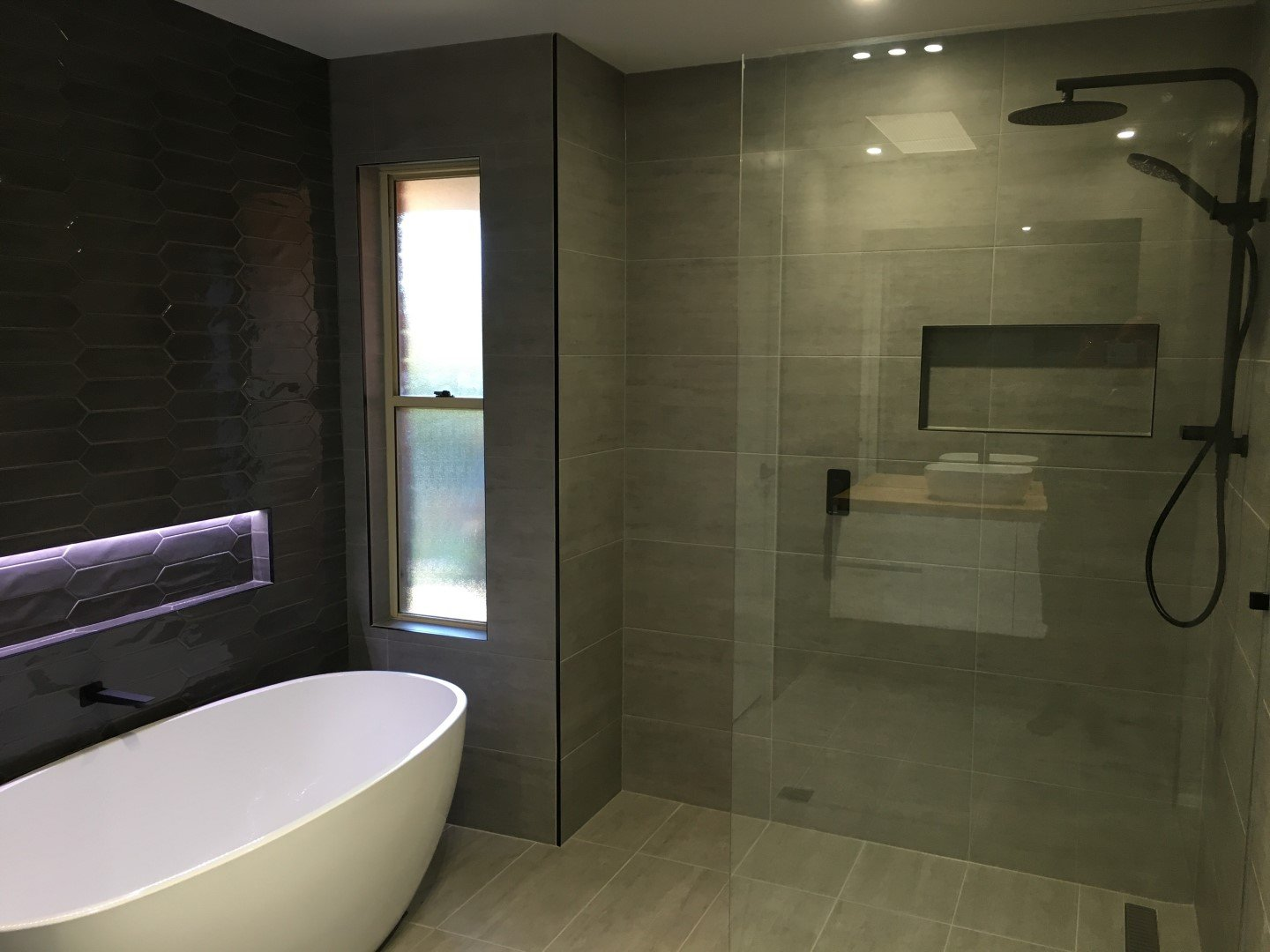 bathroom with bathtub and shower on the side with glass divider